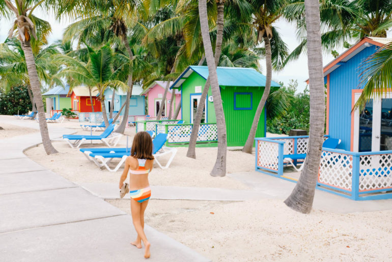 daughter walking in bathing suit by colorful bungalows