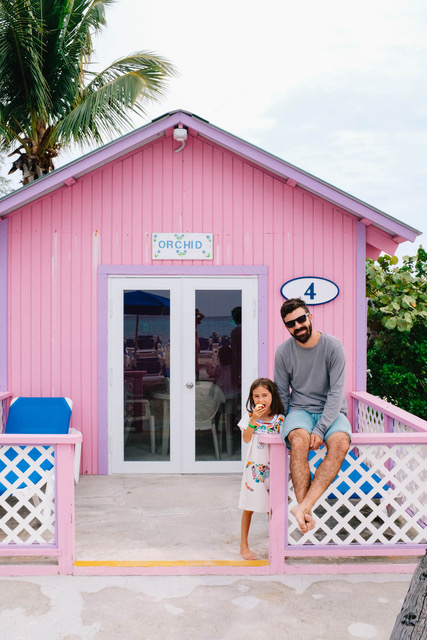 dad and daughter in front of pink bungalow
