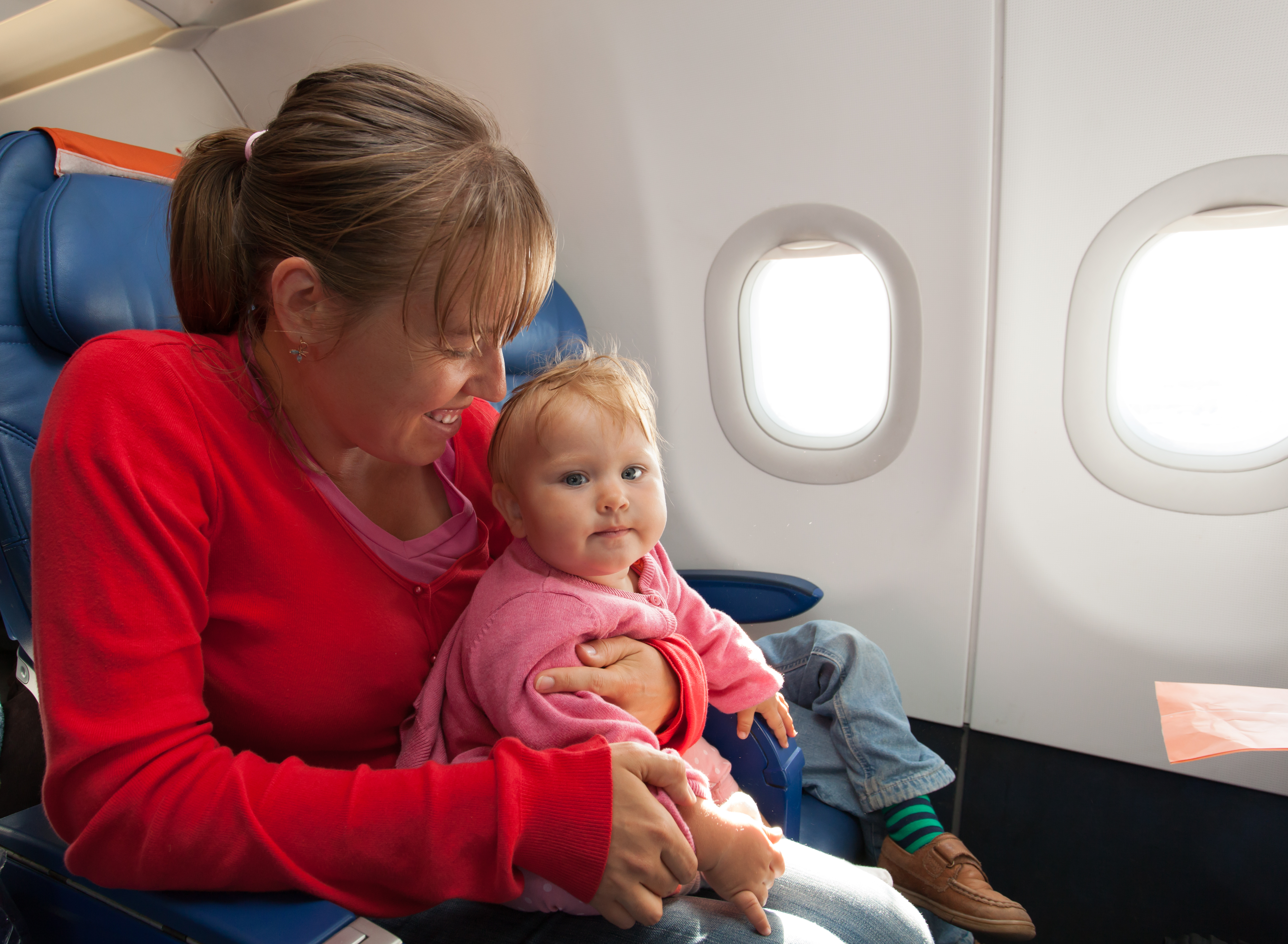 mother and little daughter travel by plane
