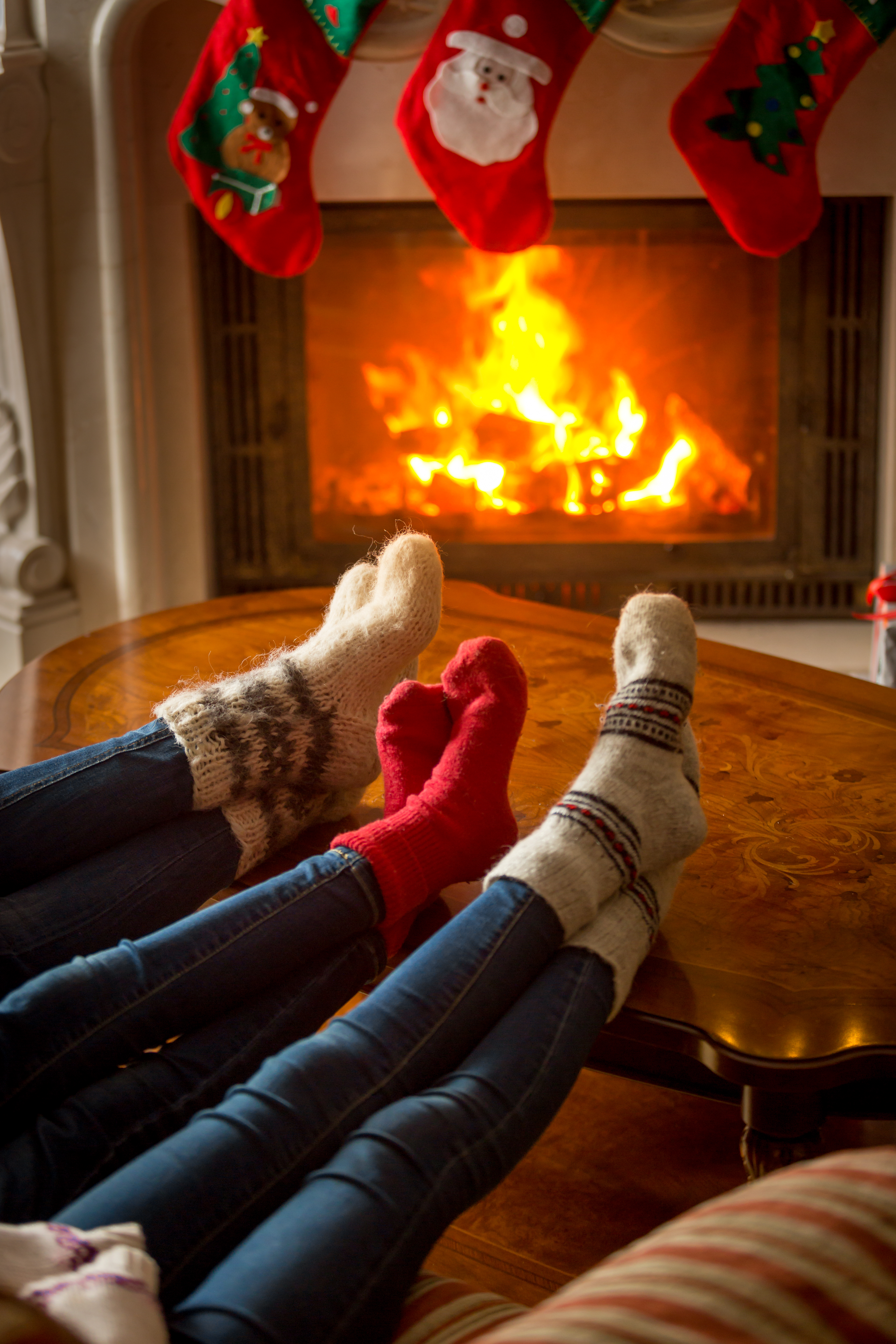 Feet in woolen socks warming at burning fireplace