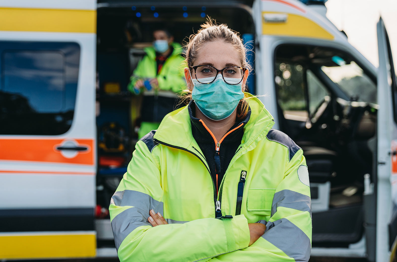 A female paramedic wearing a mask stands outside of an ambulance with its side door open