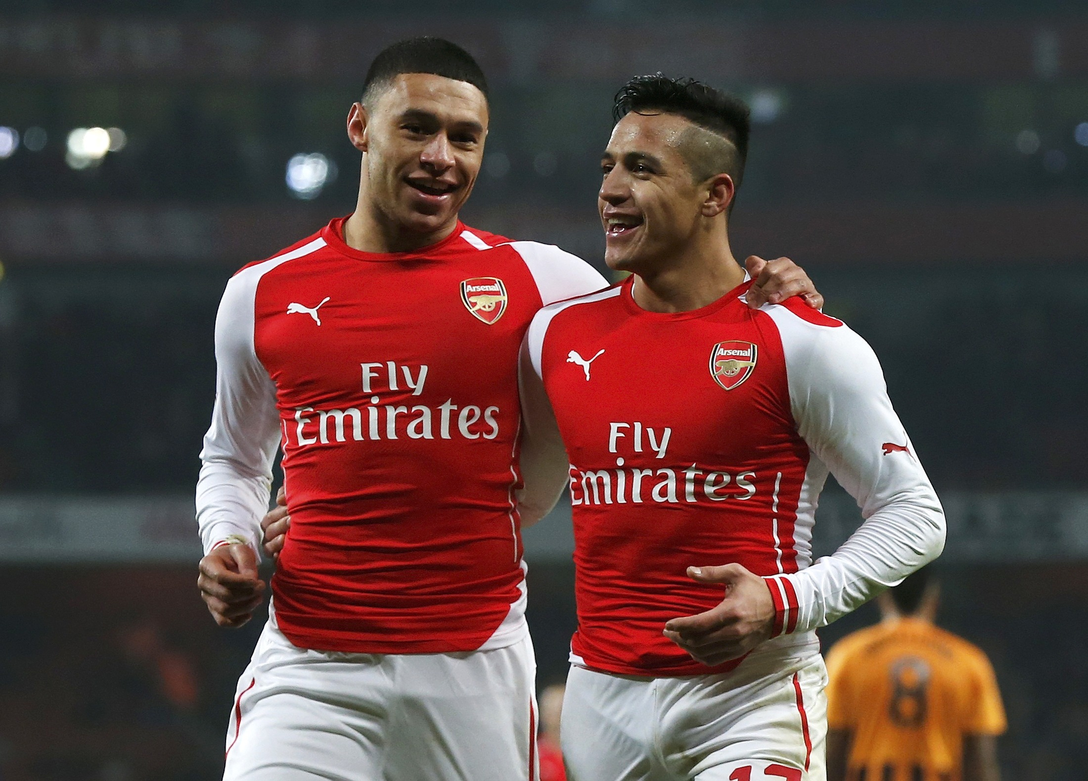 Alexis Sanchez of Arsenal celebrates with team mate Alex Oxlade-Chamberlain after scoring his team's second goal against Hull during their FA Cup third round soccer match at the Emirates Stadium in London